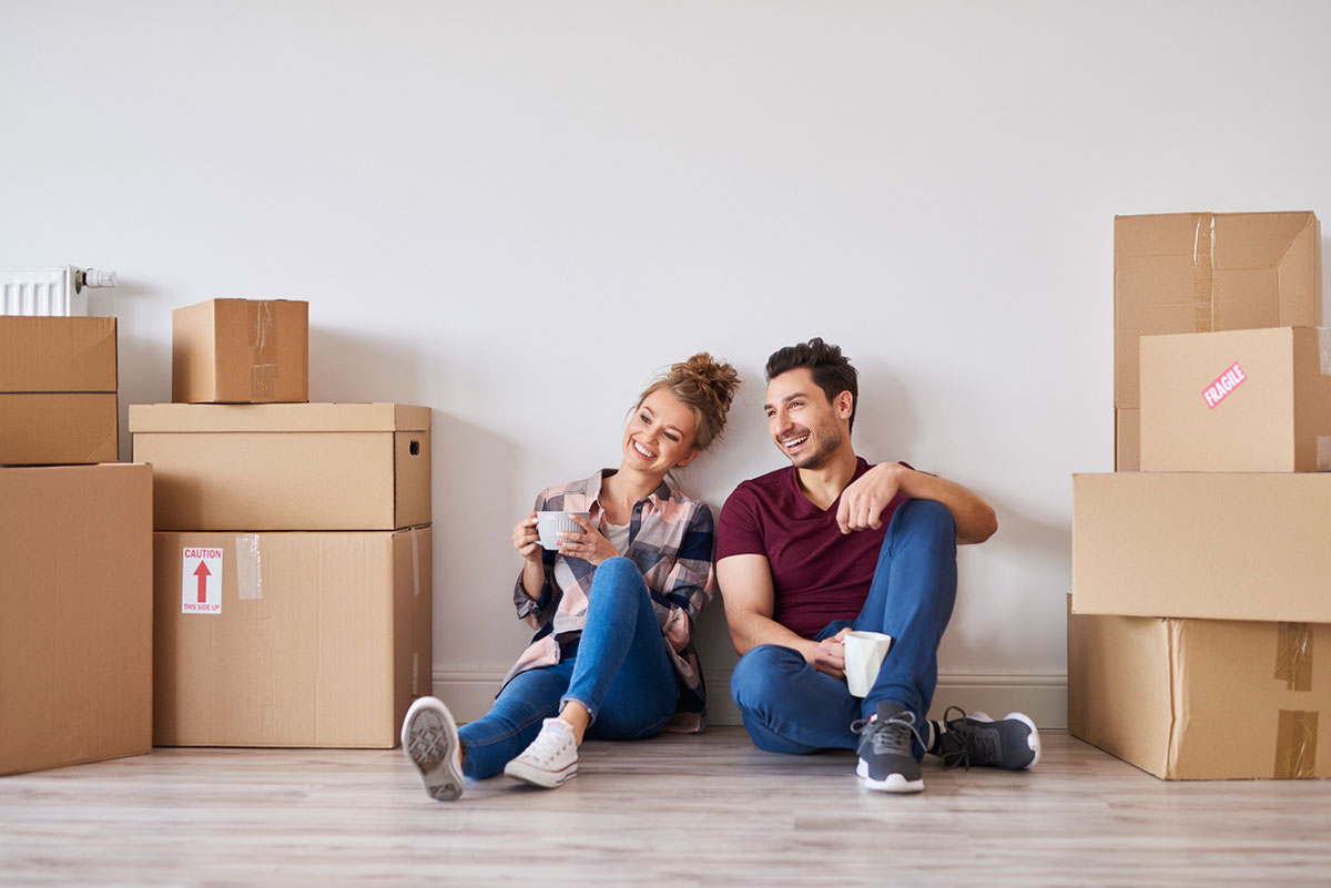 Couple sitting on the floor in new home surrounded by moving boxes
