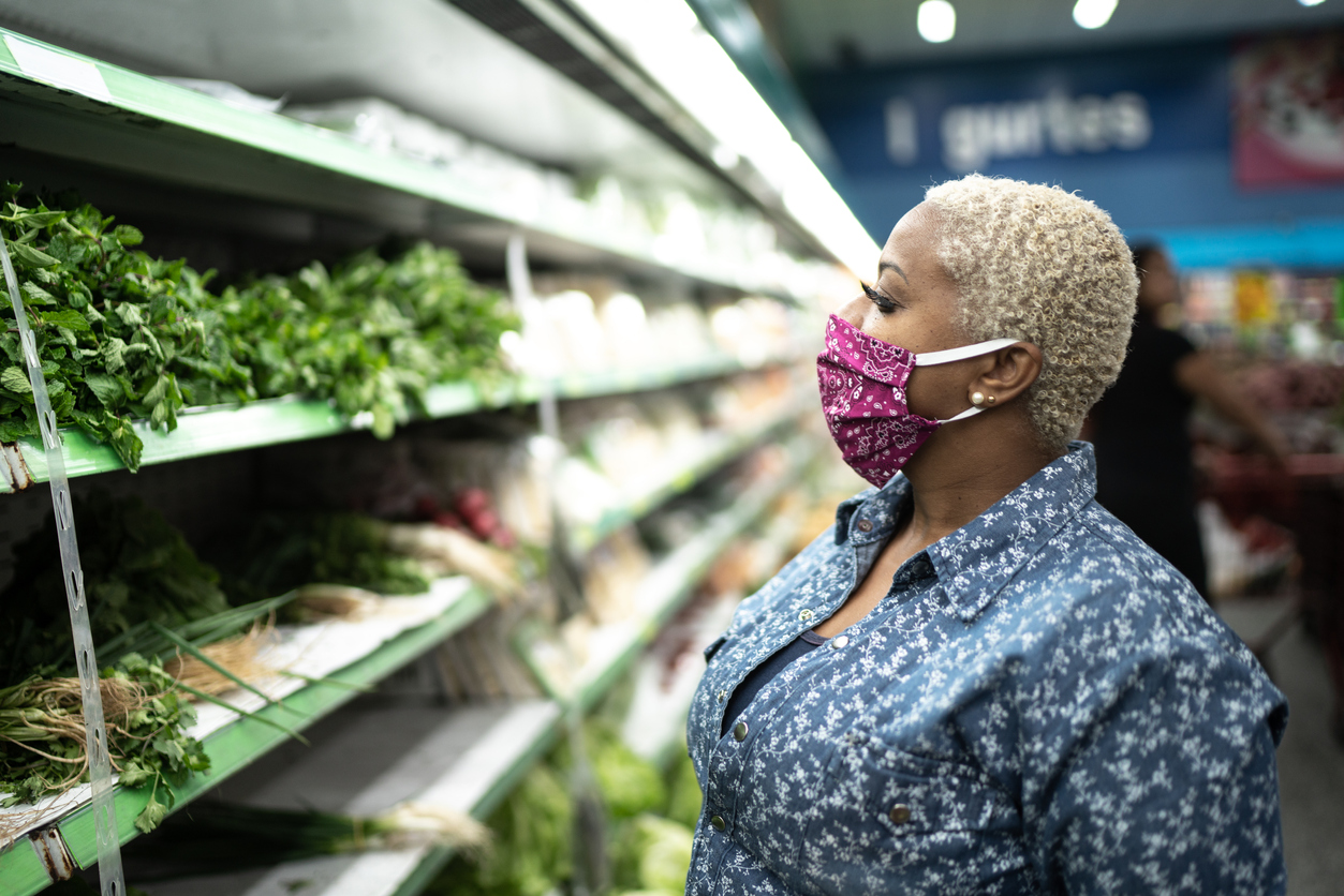 Woman in grocery store with fabric mask on